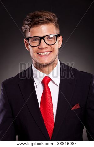 picture of a young business man with a beautiful smile on his face. on dark background
