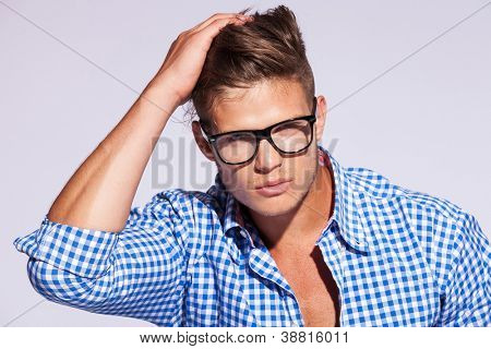 young casual fashion man wearing a shirt with eyeglasses on gray background