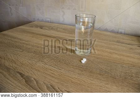 Pills On Table In Clinic Next To Glass Of Water.