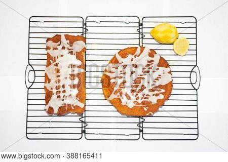 Two Freshly Baked Home Made Lemon Drizzle Cakes With Criss Cross Icing And Cut Lemon At The Side On