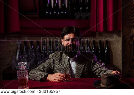 Man With Beard Holds Glass Brandy, Drink Cognac In Pub. Guy Hipster Tastes Drink. Sipping Whiskey. L