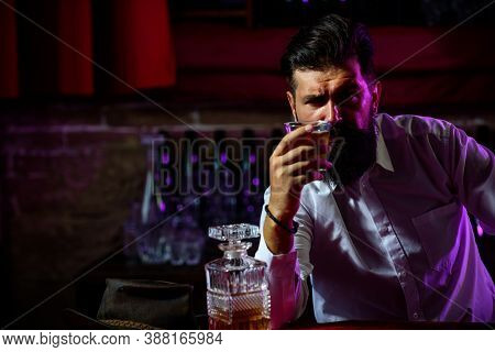 Young Man Holding Glass Of Whiskey. Guy With Beard Holds Brandy. Bearded Drink Cognac. Sommelier Tas