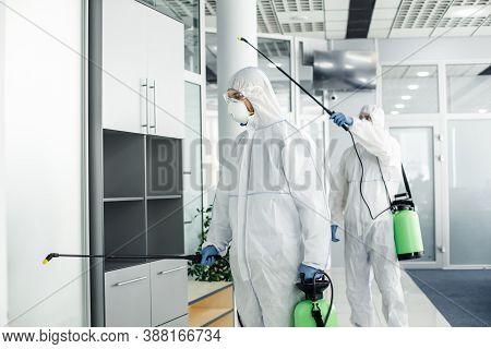 Professional Disinfection Of Room And Furniture During Coronavirus Epidemic. Men In Hazmat Suits, Pr