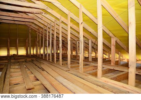A Close-up On An Unfinished Attic Construction With Wooden Roof Beams, Planks, Rafters, Ceiling Jois
