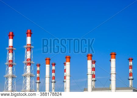A Lot Of White And Red Industrial Pipes Against The Background Of A Cloudless Blue Sky On A Sunny Da