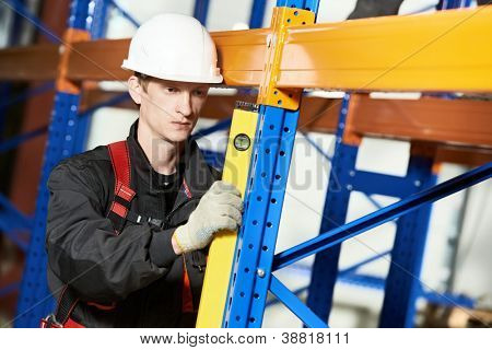 One warehouse worker in uniform with level examining quality of rack installation