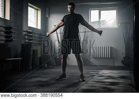 Sportive Man Stretch His Arms With Skipping Rope .