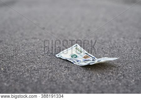 Lost Money On The Road. One Hundred Dollar Bill On The Pavement