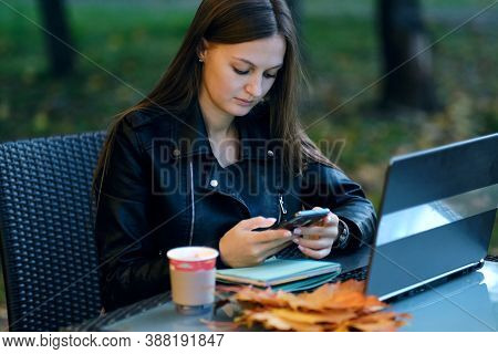 Smiling Woman Browsing The Internet. Young Lady Browsing The Internet At The Cafe. Young Woman Using