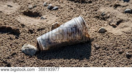 Plastic Glass Lies On The Beach And Pollutes The Sea, River. Garbage Rubbish Trash Problem Environme