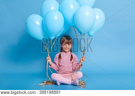Dark Haired Female Child With Two Pigtails Looking At Camera With Cute Smile, Holding Bunches In Hel