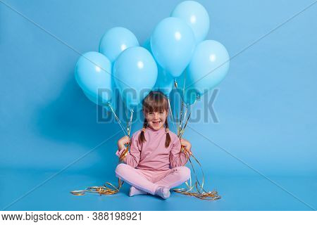 Cute Little Girl Sitting On Floor With Bunches Of Helium Balloons, Looks At Camera And Laughing, Wea