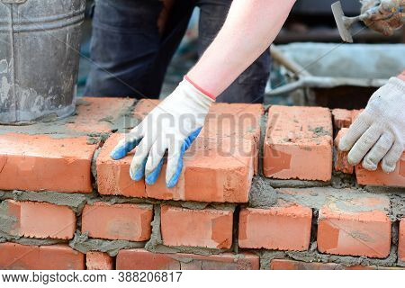 Masonry Concept. Contractors Laying Red Brick House Wall. Bricklaying Works