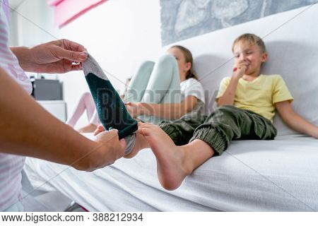 Mom Helps The Little Boy Take Off His Socks And Lightly Tickles His Feet. The Boy Giggles.