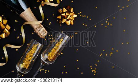 Christmas Champagne Bottle And Drink Glasses With Glittering Confetti And Golden Decorations On Blac