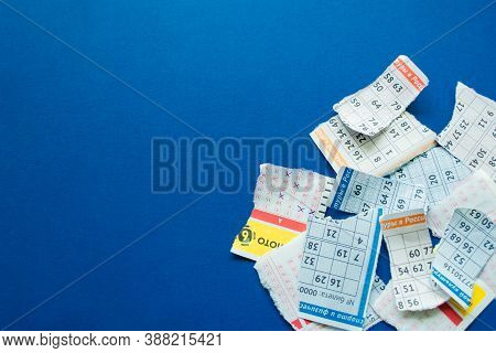 Moscow, Russia, July 2020: Torn Lottery Tickets With Numbers On A Dark Blue Background. On The Piece