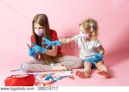 Personal Protective Equipment: Two Girls In Medical Masks And Gloves Play Doctor And Use A Medical K