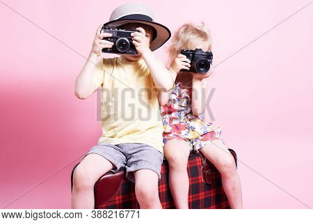 Travel: Children A Little Boy And Girl Play In Tourists, Sit On A Big Red Suitcase And Take Pictures