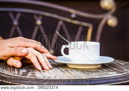 Ouple Holding Hands, A Cup Of Hot Coffee. Couple Enjoying Coffe. Female And Man Hands Holding Cup Of