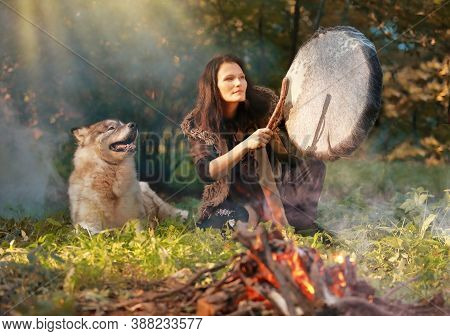 Shaman Woman Playing Her Shaman Sacred Drum In The Sunny Forest Against The Background Of Nature, Th