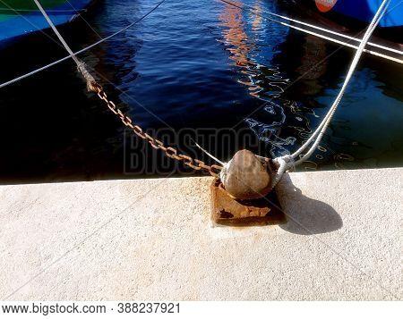Ship Mooring Ropes Secured Around A Port Bollard