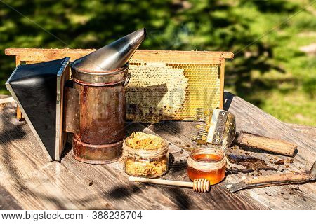 Jar Of Fresh Honey In A Glass Jar, Beekeeping Tools Outside. Frame With Bees Wax Structure Full Of F