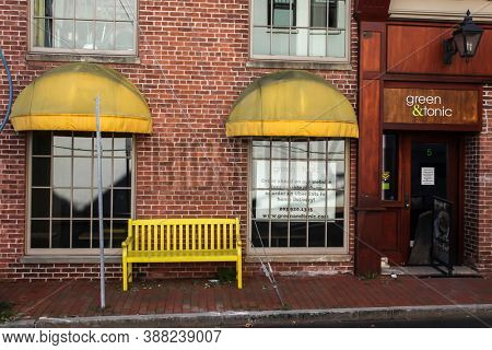 NEW CANAAN, CT, USA - OCTOBER 4, 2020: Green & tonic storefront with yeallow seatbench on Burtis Avenue in downtown