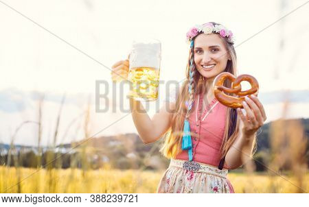 Bavarian woman with beer and pretzel in beautiful landscape during sunset