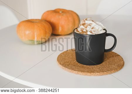 Pumpkin Spice Latte With Whipped Cream And Cinnamon Powder In A Black Coffee Mug Served On Cork Coas
