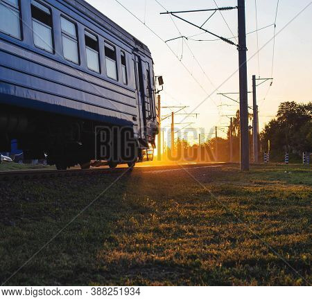 Passenger Train For Transporting People Moves On The Railroad Against The Background Of Sunset, Copy