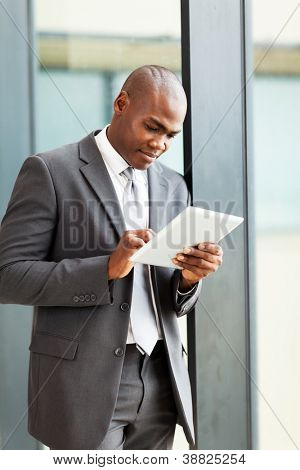 thoughtful african american businessman with tablet computer in office