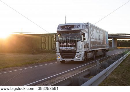 Bobruisk, Belarus 26.06.2019: A Truck With A Trailer Transports Cargo On The Highway At Sunset