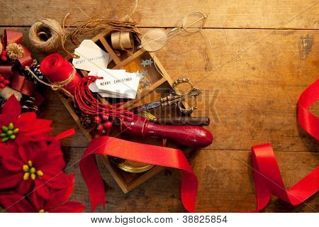 Christmas preparation. Tray with ribbons and christmas tags, on an old wooden table with vintage feel. Warm incandescent lighting.