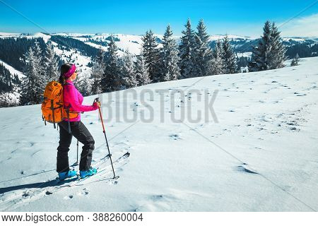 Backcountry Skiing On The Snowy Hills. Sporty Happy Woman With Colorful Backpack, Ski Touring In The