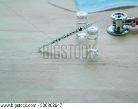 Syringe And Vaccine Or Medicine Bottles Blure Stethoscope  As Background