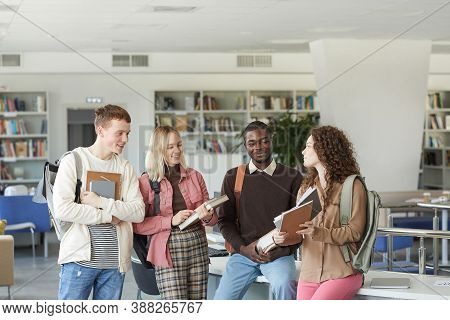 Portrait Of Multi-ethnic Group Of Students Standing In College Library And Chatting While Holding Bo