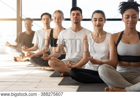 Group Meditation. Sporty Young Multiracial Men And Women Meditating Together During Yoga Class In Mo