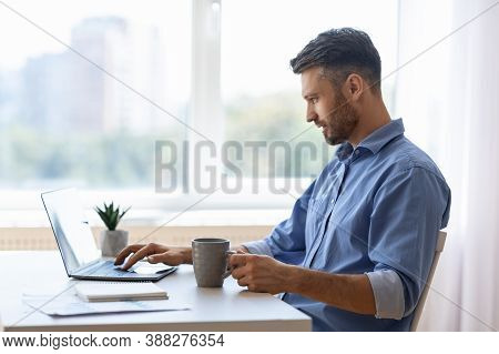 Remote Work. Handsome Male Freelancer Using Laptop And Drinking Coffee, Working Remotely At Home Off