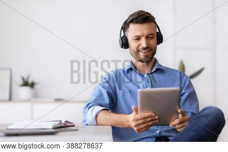 Handsome Businessman In Headphones Relaxing At Workplace With Digital Tablet, Having Break, Sitting