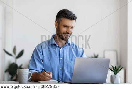 Millennial Male Entrepreneur Using Laptop And Taking Notes At Workplace In Modern Office, Looking At