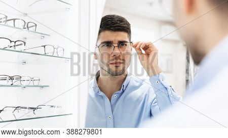 Choosing Glasses Concept. Over The Shoulder Portrait Of Handsome Bearded Guy Picking New Eyewear At