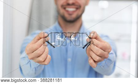 Eyewear Choice Concept. Closeup Of Unrecognizable Smiling Guy Client Holding And Showing New Spectac