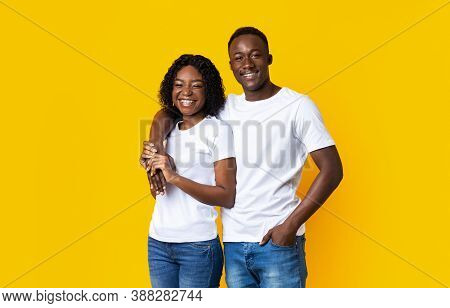 Cheerful Loving Black Couple Embracing And Smiling On Yellow Background. Happy Young African America