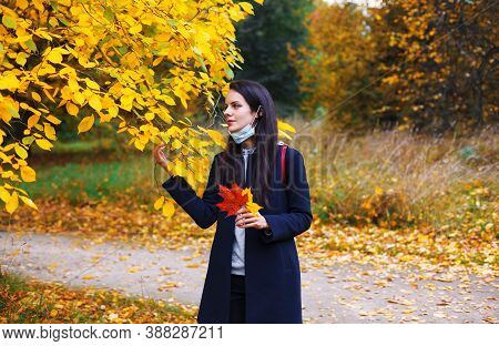 Woman With Lowered Protective Mask Walks In Autumn Park. Spending Time At Nature During Coronavirus