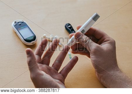 Close Up Of A Man's Hand Using A Lancet On His Finger To Check Blood Sugar Using A Glucose Meter, Us
