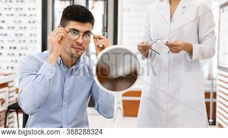 Vision Correction Concept. Female Optometrist Helping Male Client To Choose Eyeglasses For Computer,