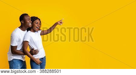 Joyful African-american Couple Smiling And Cheerfully Pointing Away At Empty Space, Yellow Studio Ba