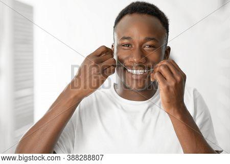Happy African American Man Flossing Teeth Standing In Modern Bathroom At Home, Smiling Looking At Ca