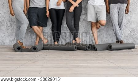 Before Yoga Class. Cropped Image Of Diverse Multiracial People In Sportswear Standing Near Yoga Mats