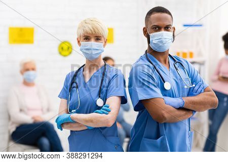 Portrait Of Two Diverse Doctors In Protective Masks Posing Looking At Camera Standing In Hospital Wa